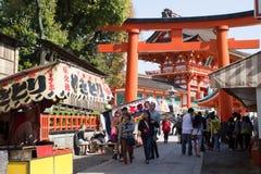 Uma porta gigante do torii na frente da porta de Romon na entrada do santuário de Fushimi Inari Imagem de Stock