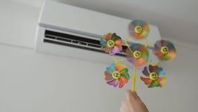 Uma posição adulta do homem na frente do condicionador de ar que guarda um brinquedo das crianças com uma hélice de gerencio vídeos de arquivo