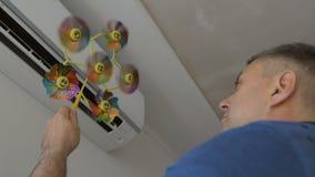 Uma posição adulta do homem na frente do condicionador de ar que guarda um brinquedo das crianças com uma hélice de gerencio video estoque