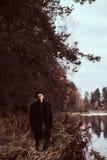 Uma posição considerável do homem novo na floresta do outono foto de stock