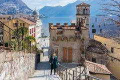 Uma posição da jovem mulher na frente de uma construção velha da arquitetura na cidade de Lugano, Suíça imagens de stock royalty free