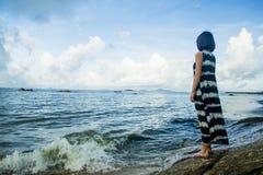 Uma posição da menina pelo mar fotos de stock royalty free