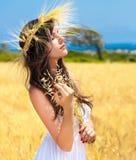 Uma posição da mulher no campo com uma grinalda imagens de stock royalty free