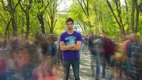 Uma posição da pessoa outcropped na multidão de povos, em árvores do verde do fundo A câmera está aproximando-se Lapso de tempo filme