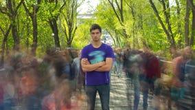 Uma posição da pessoa outcropped na multidão de povos, em árvores do verde do fundo Lapso de tempo A câmera afasta-se filme