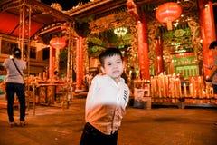 Uma posição do menino em Dragon Temple Kammalawat, o 9 de fevereiro de 2013 na estrada Banguecoque de Yaowarat, Tailândia foto de stock