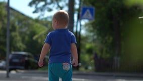 Uma posição do rapaz pequeno em uma rua da cidade entre bolhas de sabão no movimento lento video estoque