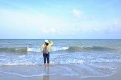 Uma posição fêmea na praia do mar com ondas de água e as nuvens brancas do céu azul fotos de stock