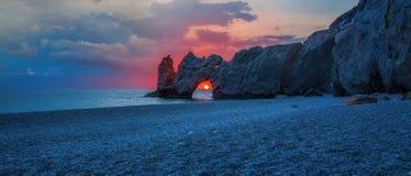 Uma praia bonita no nascer do sol com o sol no furo das rochas fotografia de stock