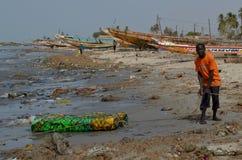 Uma praia coberta pela maca plástica no pequeno CÃ'te de Senegal, África ocidental imagens de stock