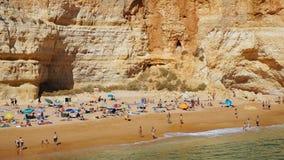 Uma praia contra uma rocha grande imagem de stock royalty free