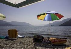 Uma praia do lago com pára-sóis e deckchairs, e inflatabl Fotografia de Stock