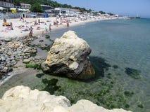 Uma praia do mar com muitos povos e rochas Fotos de Stock