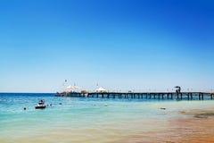 Uma praia do mar e um cais que estenda na distância contra um céu ensolarado azul fotografia de stock