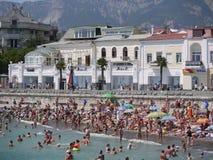 Uma praia pequena no litoral é embalada com povos No fundo, em lojas do branco e em outros estabelecimentos imagens de stock
