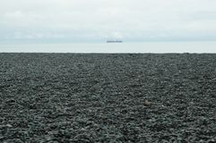 Uma praia seixoso que conduz a um mar prata-azul Fotografia de Stock