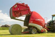 Uma prensa redonda descarrega um pacote de feno durante a colheita Imagens de Stock