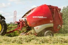 Uma prensa redonda que faz pacotes do pacote de feno durante a colheita Fotografia de Stock