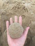 Uma protuberância da areia na palma de sua mão imagem de stock royalty free