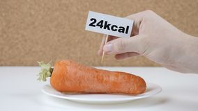 Uma quantidade de calorias na cenoura, a mão masculina põe uma placa com o número de calorias sobre uma cenoura ilustração royalty free