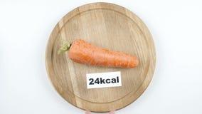 Uma quantidade de calorias na cenoura, a mão masculina põe uma placa com o número de calorias sobre uma cenoura, tiro superior ilustração do vetor