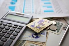Uma quantidade grande de moeda e de calculadora dos E.U. com documento financeiro imagens de stock royalty free