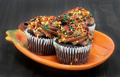 Uma queda de três chocolates decorou queques em uma placa da abóbora Imagem de Stock Royalty Free