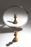 Uma rainha branca está olhando em um espelho para ver-se como uma rainha preta imagem de stock