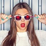 Uma rapariga bonita com os dois pirulitos vermelhos perto da parede Imagem de Stock