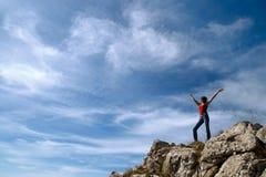 Uma rapariga está na borda de um penhasco Fotografia de Stock Royalty Free