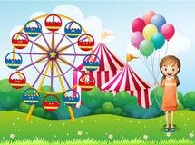 Uma rapariga feliz que guardara balões perto do carnaval Fotografia de Stock Royalty Free