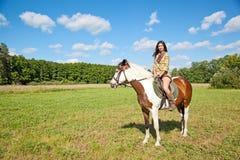 Uma rapariga monta um cavalo da pintura fotos de stock