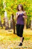 Uma rapariga que funciona no parque do outono Fotos de Stock