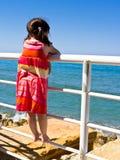 Uma rapariga que olha para fora ao mar Imagens de Stock Royalty Free