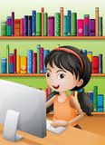 Uma rapariga que usa o computador na biblioteca Fotos de Stock Royalty Free