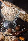 Uma refeição seca saudável da aveia com porca em uma colher de madeira Fotos de Stock