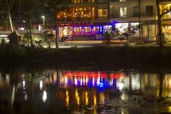 Uma reflexão colorida no lago das luzes da cidade da noite na costa fotografia de stock royalty free