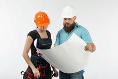 Uma reunião masculina do arquiteto ou do coordenador com um contratante da mulher da construção no fundo branco fotos de stock royalty free