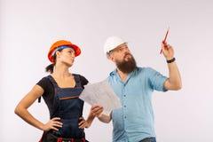 Uma reunião masculina do arquiteto ou do coordenador com um contratante da mulher da construção no fundo branco fotos de stock