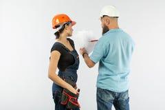 Uma reunião masculina do arquiteto ou do coordenador com um contratante da mulher da construção no fundo branco fotografia de stock