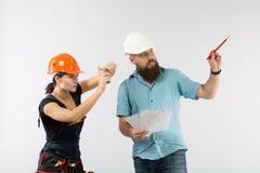 Uma reunião masculina do arquiteto ou do coordenador com um contratante da mulher da construção no fundo branco imagens de stock