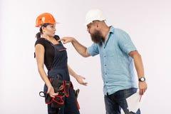 Uma reunião masculina do arquiteto ou do coordenador com um contratante da mulher da construção no fundo branco foto de stock royalty free