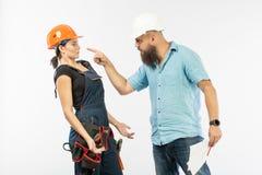 Uma reunião masculina do arquiteto ou do coordenador com um contratante da mulher da construção no fundo branco imagens de stock royalty free