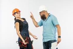 Uma reunião masculina do arquiteto ou do coordenador com um contratante da mulher da construção no fundo branco foto de stock