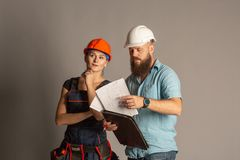 Uma reunião masculina do arquiteto ou do coordenador com um contratante da mulher da construção no fundo cinzento fotos de stock