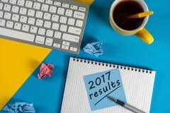 uma revisão de 2017 anos na prancheta e no café contra a tabela amarela e azul com teclado Foto de Stock