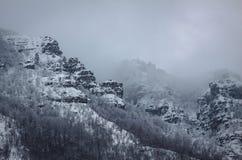 Uma rocha da montanha coberta com a neve Imagens de Stock