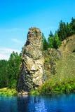 Uma rocha no banco Imagens de Stock