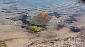 Uma rocha no centro de um mar trasparent Fotografia de Stock