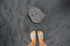 Uma rocha preta da lava na praia preta da areia imagens de stock
